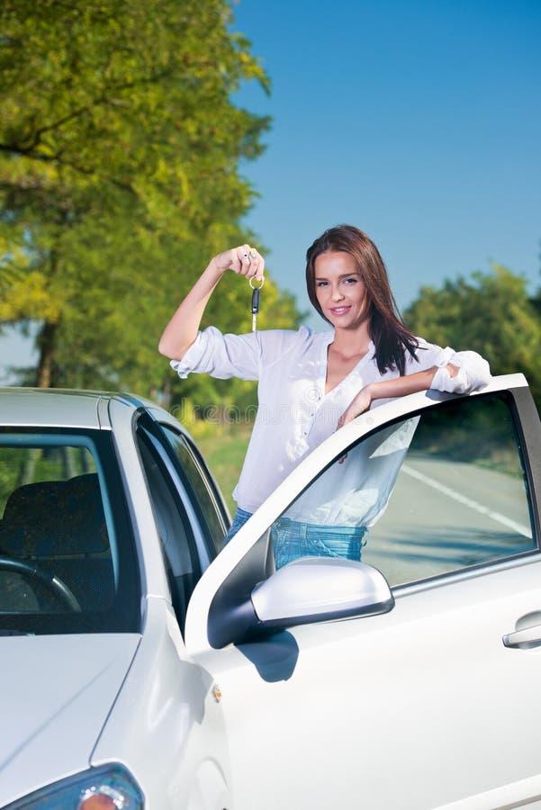 Bella donna che sta accanto alle chiavi di una tenuta dell'automobile fotografie stock