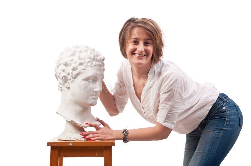 Bella donna che sta la statua antica vicina ed i tocchi dell'uomo il suo immagine stock