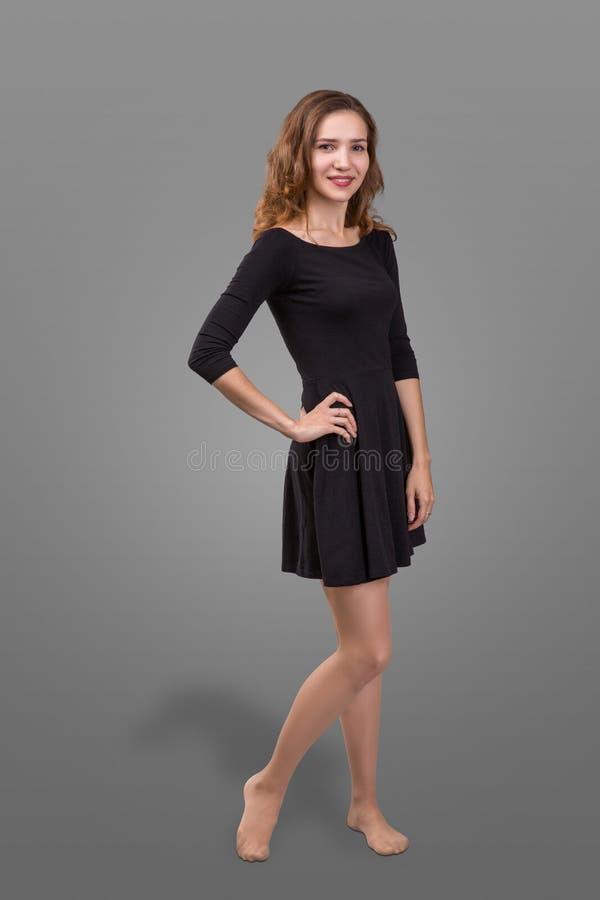 Bella donna che sta in un vestito nero sopra fondo grigio immagini stock libere da diritti