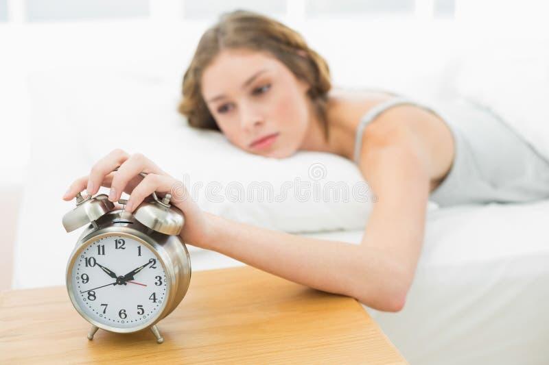 Bella donna che sveglia mentre trovandosi nel suo letto fotografia stock