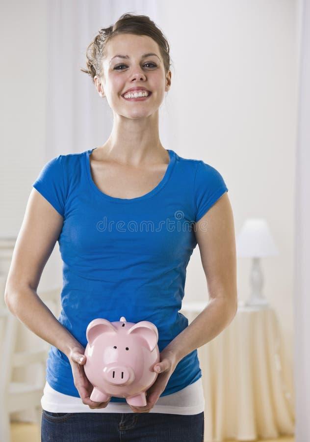 Bella donna che tiene banca piggy. fotografia stock