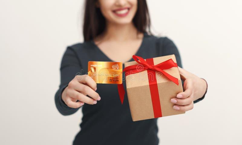 Bella donna che tiene la carta di credito ed il contenitore di regalo fotografie stock libere da diritti