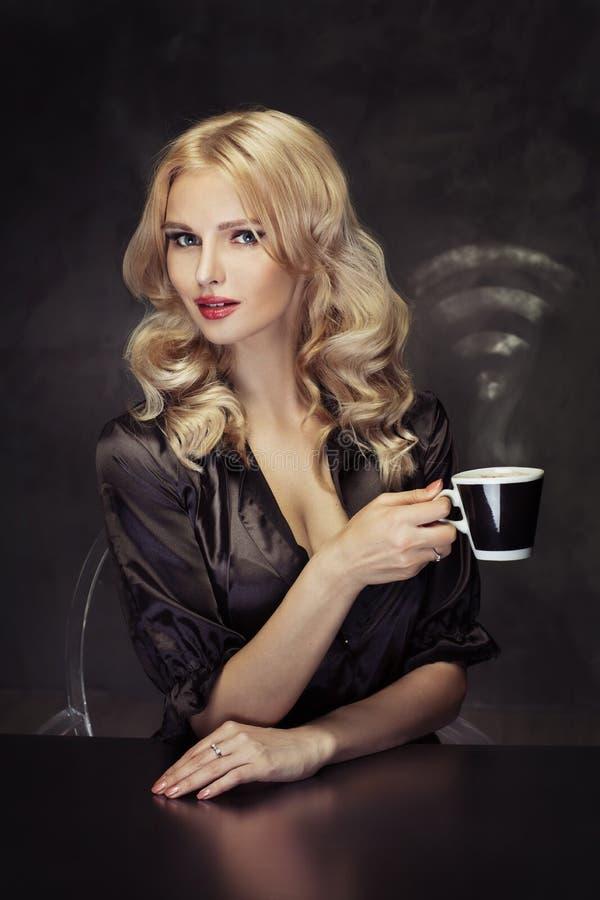 Bella donna che tiene la tazza di caffè vaporous immagine stock libera da diritti