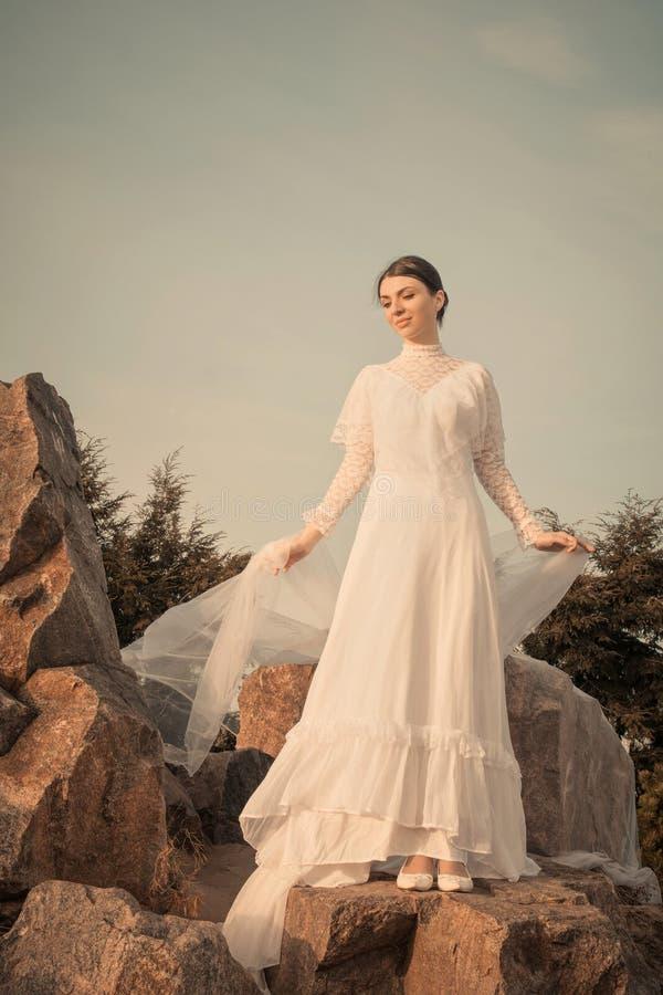 Bella donna che tiene sciarpa bianca sul fondo di tramonto immagine stock
