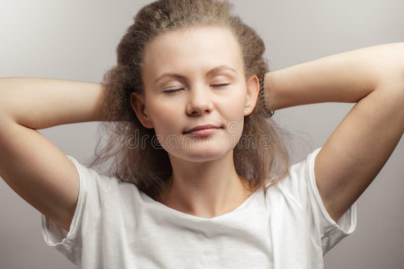 Bella donna che tocca i suoi capelli lanuginosi giusti dopo la mostra immagine stock