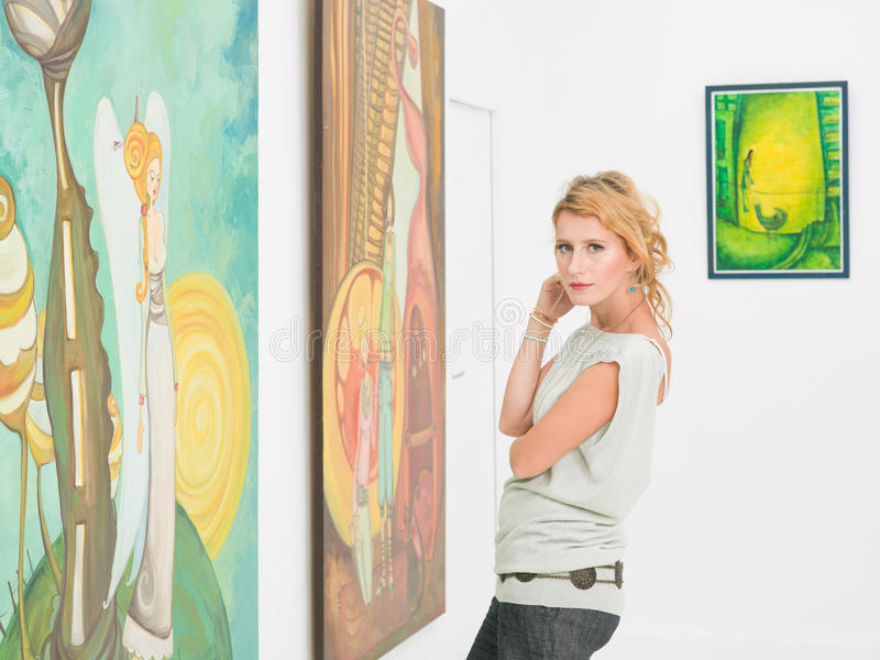 Bella donna che visita una galleria di arte fotografia stock