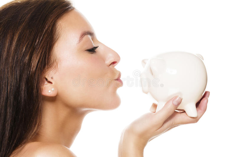 Bella donna circa per baciare una banca piggy immagine stock