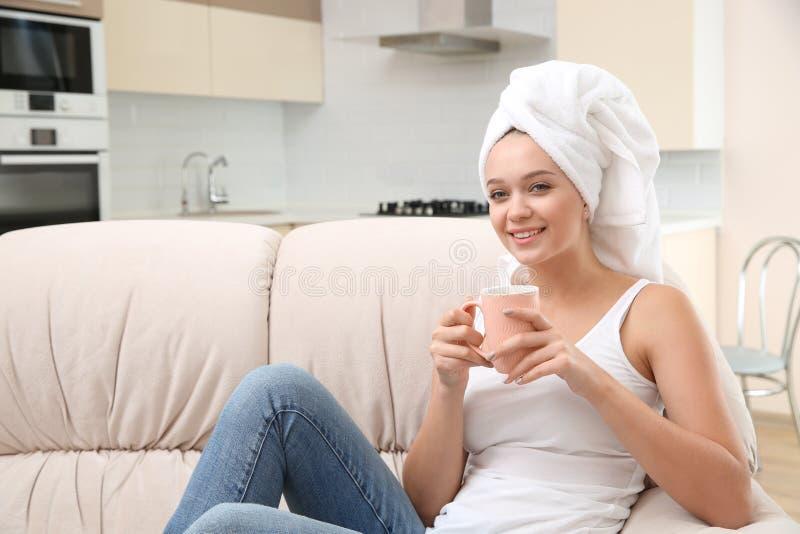 Bella donna con capelli avvolti in asciugamano che si siede sul sofà e sul tè bevente immagini stock
