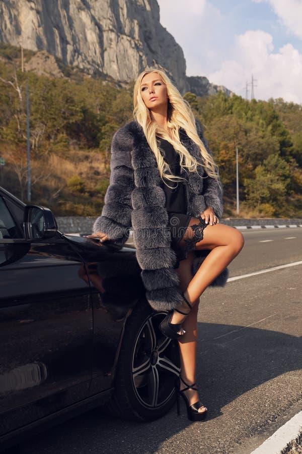 Bella donna con capelli biondi in attrezzatura elegante, posante sulla strada immagini stock