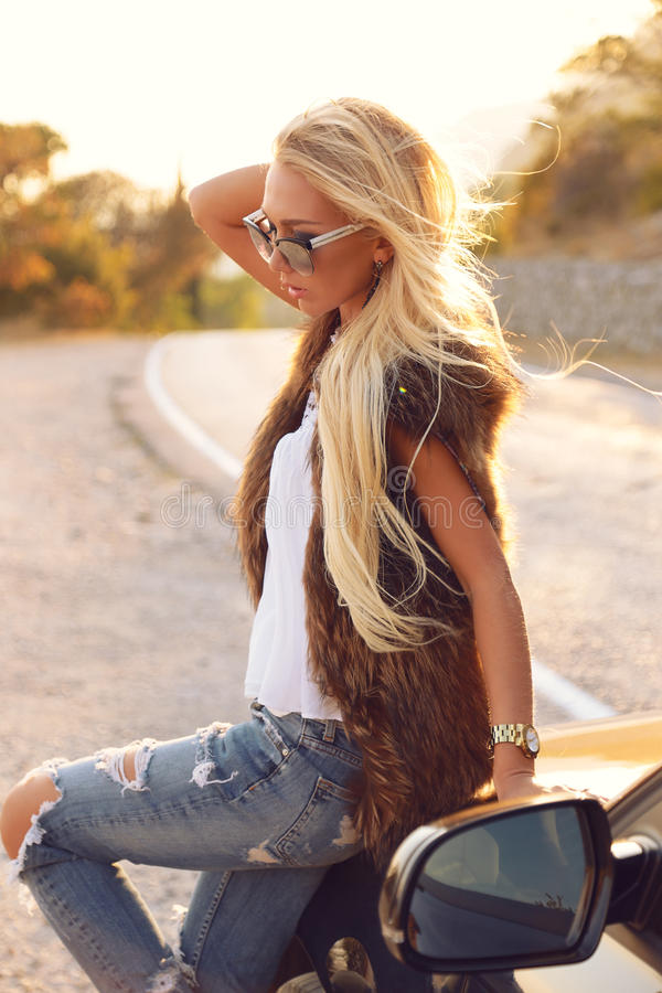 Bella donna con capelli biondi in attrezzatura elegante, posante sulla strada immagine stock libera da diritti