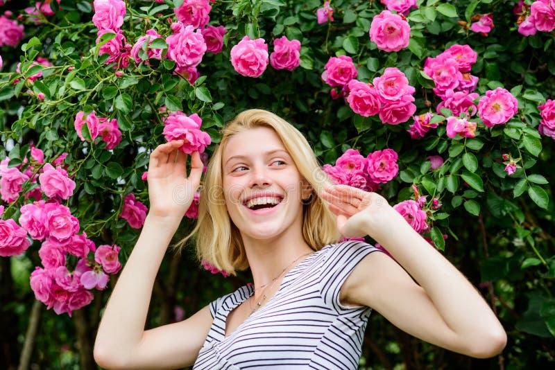 Bella donna con capelli biondi in giardino natura del parco della primavera e di estate odore rosa del fiore Parfume Bellezza nat fotografia stock libera da diritti