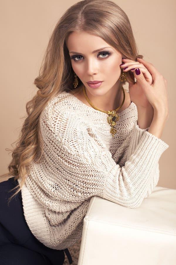 Bella donna con capelli biondi lunghi in maglione beige fotografie stock