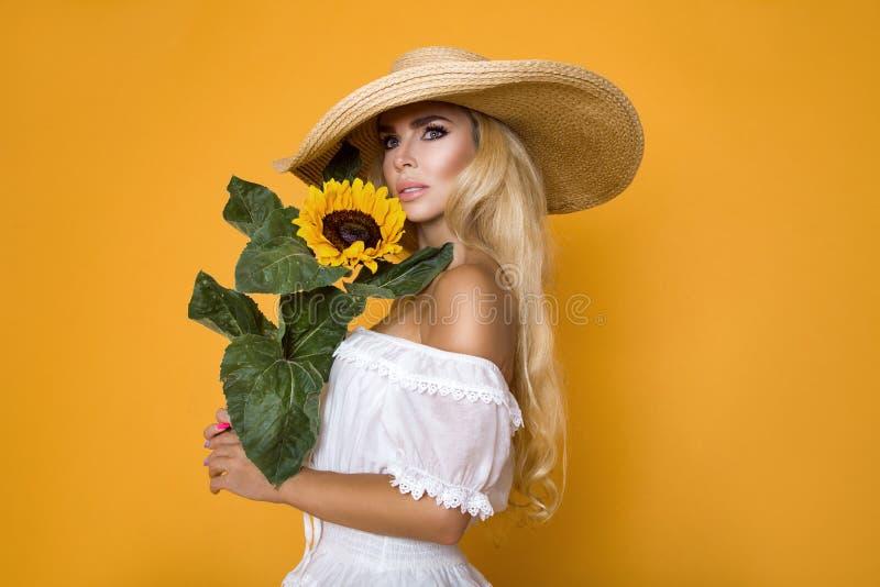 Bella donna con capelli biondi lunghi, portando un vestito e un cappello bianchi, tenenti i girasoli immagine stock libera da diritti