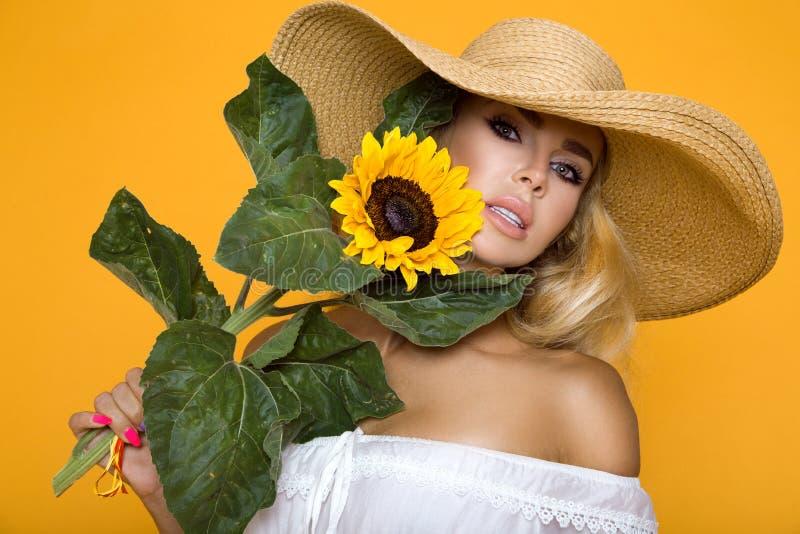 Bella donna con capelli biondi lunghi, portando un vestito e un cappello bianchi, tenenti i girasoli immagine stock
