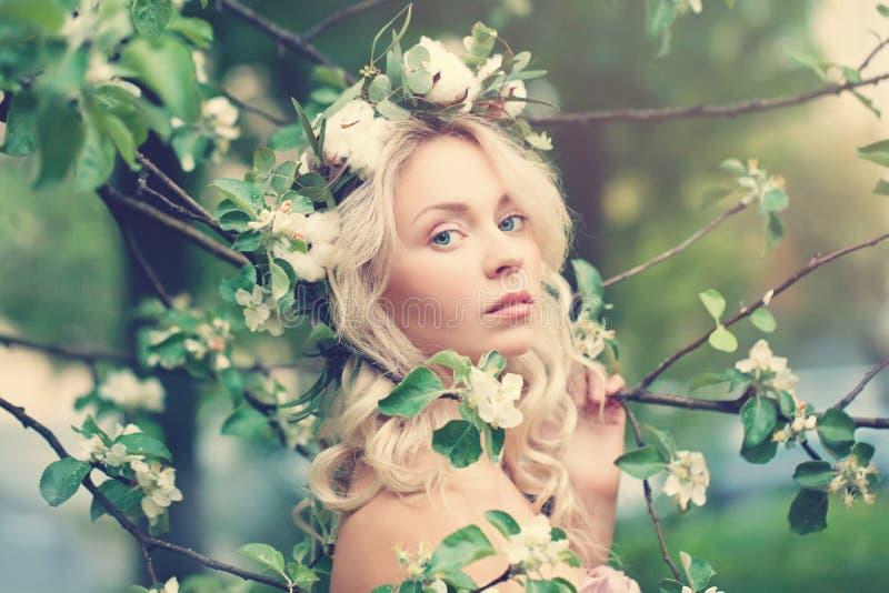 Bella donna con capelli biondi sul fondo della primavera immagine stock