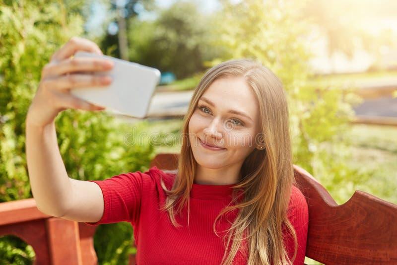 Bella donna con capelli giusti che portano maglione casuale rosso che trasforma selfie con il suo telefono cellulare che posa la  fotografia stock