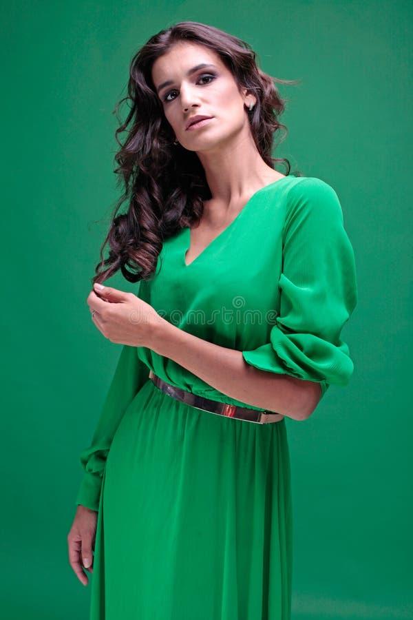 Bella donna con capelli lunghi ricci marroni in vestito verde immagini stock
