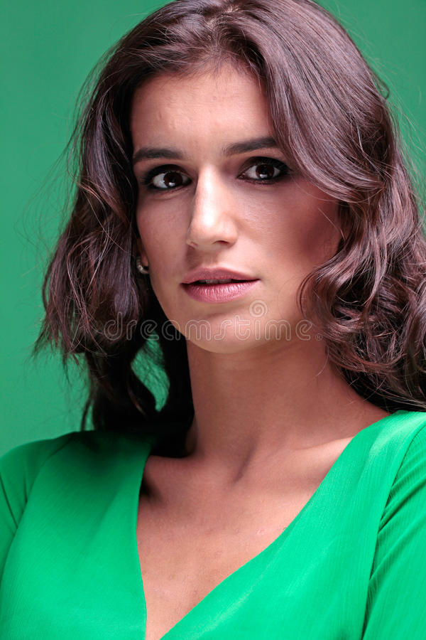 Bella donna con capelli lunghi ricci marroni in vestito verde fotografie stock libere da diritti
