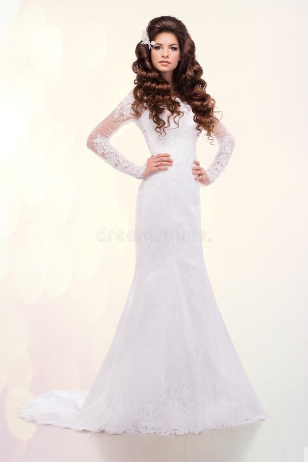 Bella donna con capelli lunghi in vestito da sposa sopra il fondo bianco dello studio fotografie stock