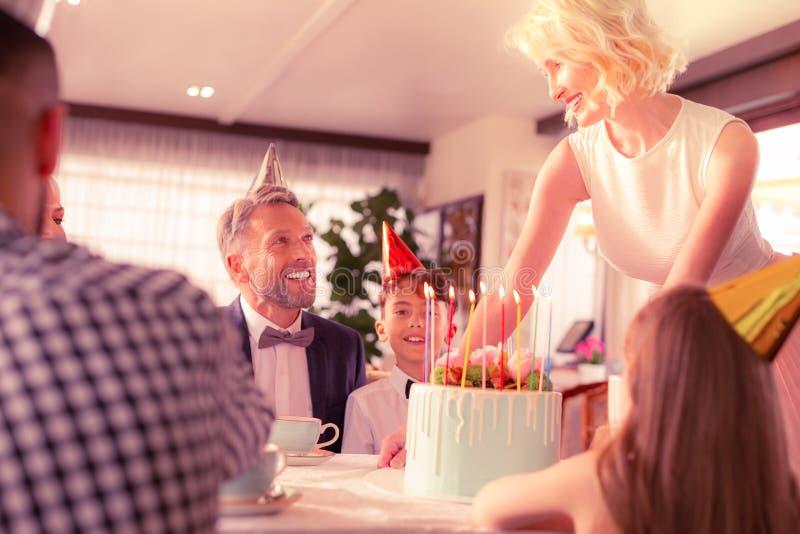 Bella donna con capelli ondulati che mettono torta di compleanno per il figlio immagine stock