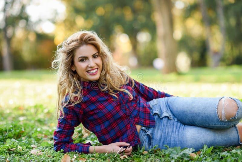 Bella donna con capelli ricci biondi lunghi in un parco fotografie stock libere da diritti