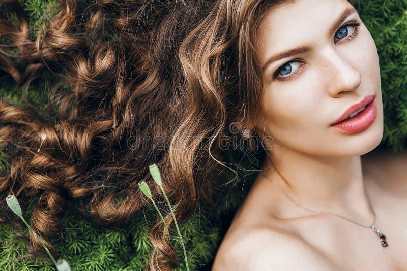 Bella donna con capelli ricci lunghi sull'erba della molla fotografia stock