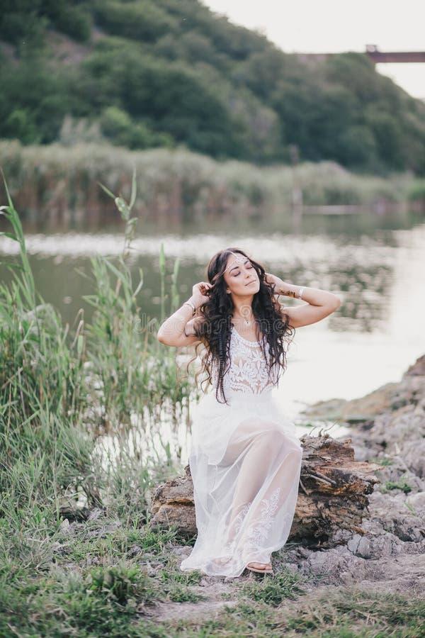 Bella donna con capelli ricci lunghi vestiti in vestito da stile di boho che posa vicino al lago immagini stock