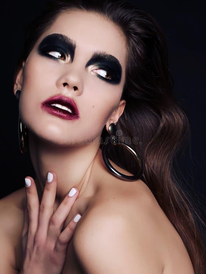 Bella donna con capelli scuri e trucco affumicato nero esagerato degli occhi fotografie stock