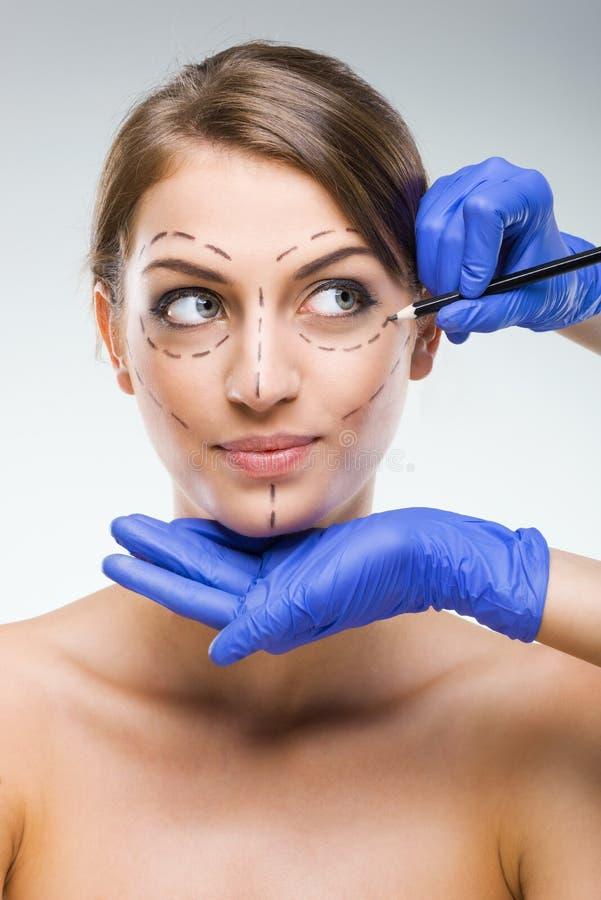 Bella donna con chirurgia plastica, dipinto, mani del chirurgo plastico fotografie stock libere da diritti