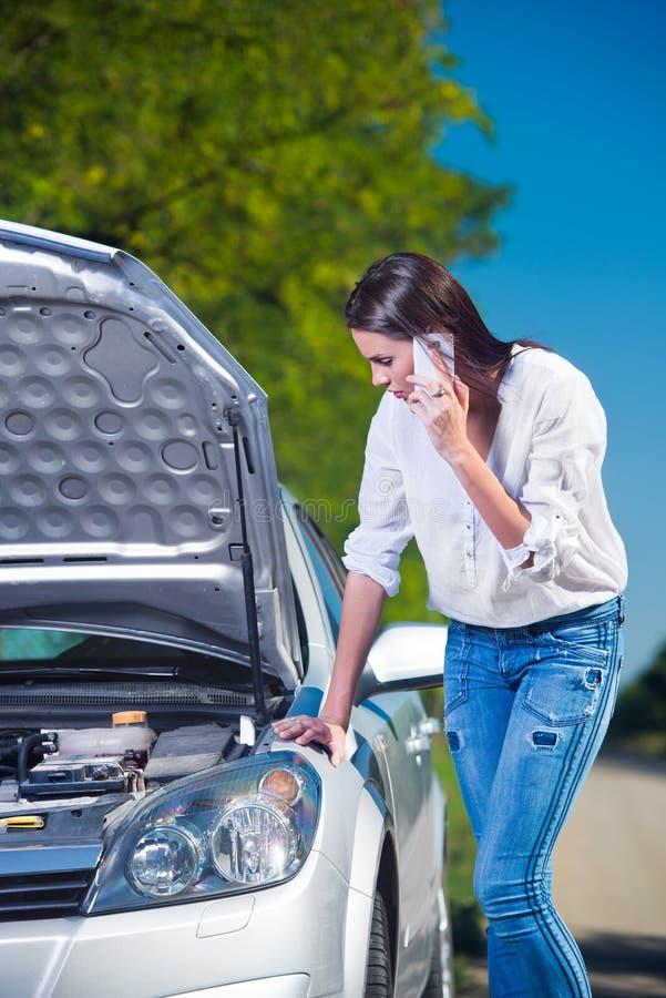Bella donna con difficoltà dell'automobile che discute a fondo telefono immagine stock libera da diritti