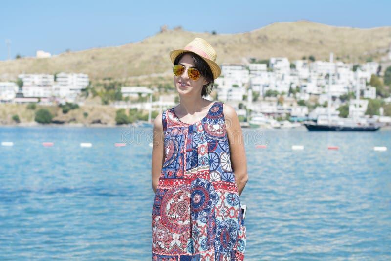 Bella donna con gli occhiali da sole dorati su un fondo del mare fotografie stock