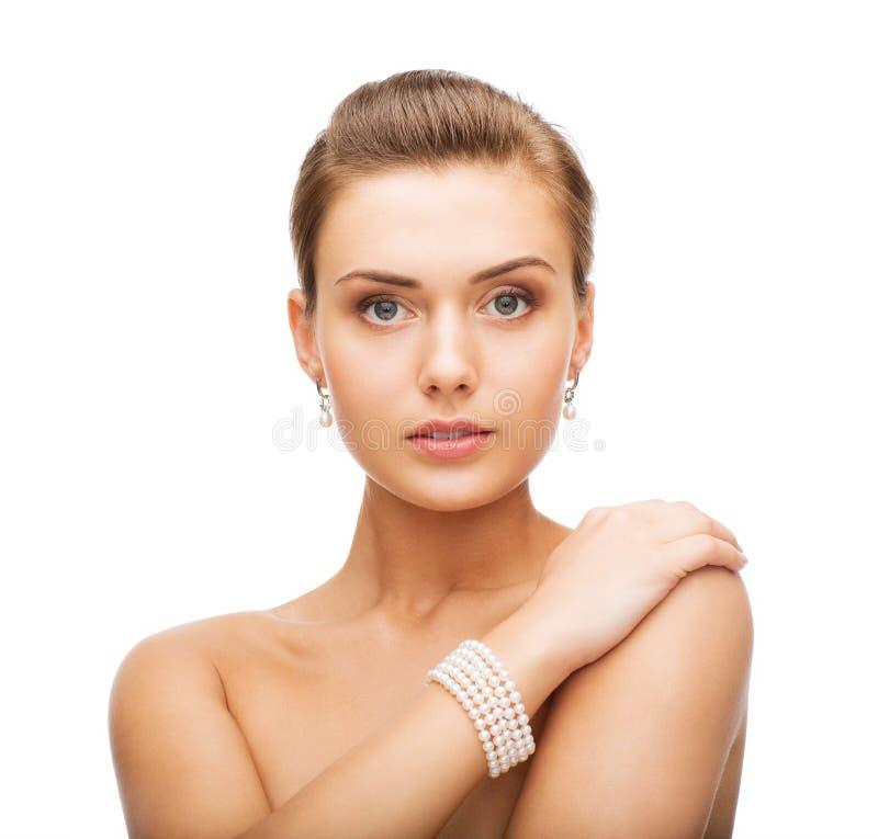 Bella donna con gli orecchini ed il braccialetto della perla immagine stock