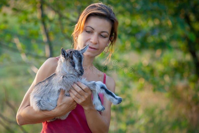 Bella donna con goatling sulle sue mani fotografia stock libera da diritti