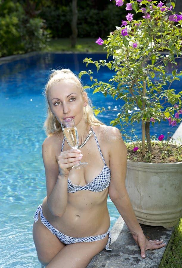 Bella donna con con i capelli biondi lunghi, una figura esile in uno swimwear del bikini circa lo stagno con acqua blu luminosa i fotografia stock