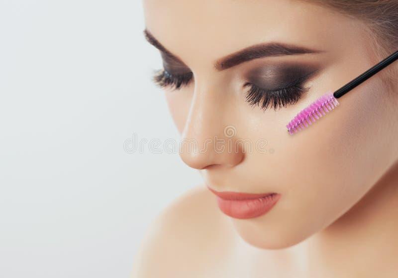 Bella donna con i cigli lunghi in un salone di bellezza Procedura di estensione del ciglio fotografie stock