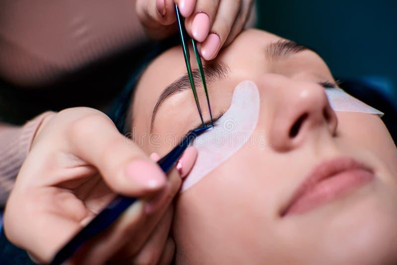 Bella donna con i cigli lunghi in un salone di bellezza Procedura di estensione del ciglio Le sferze si chiudono su immagini stock libere da diritti