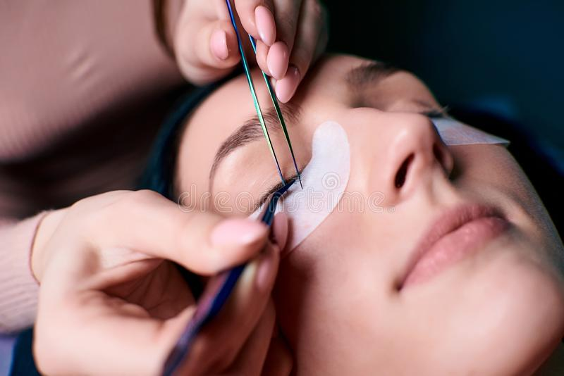 Bella donna con i cigli lunghi in un salone di bellezza Procedura di estensione del ciglio Le sferze si chiudono su fotografie stock libere da diritti