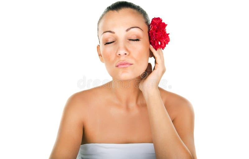 Bella donna con i fiori rossi in capelli immagine stock