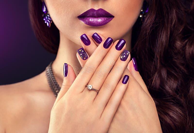 Bella donna con i gioielli d'uso del manicure porpora e di trucco perfetto immagini stock