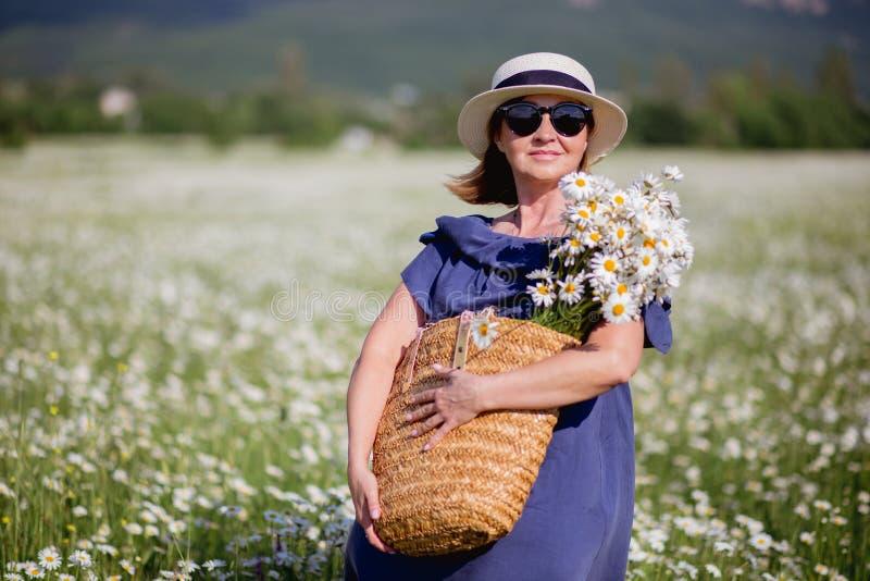 Bella donna con il canestro dei fiori sopra il campo della camomilla Donna castana felice spensierata in cappello di paglia in ve fotografie stock libere da diritti