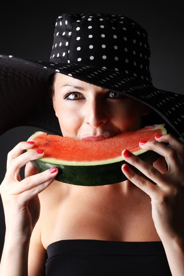 Bella donna con il cappello e l'anguria di cibo su fondo nero immagine stock