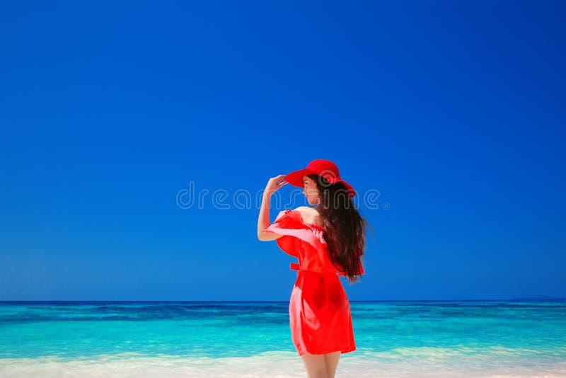 Bella donna con il cappello rosso che gode sulla spiaggia tropicale, modo fotografie stock libere da diritti