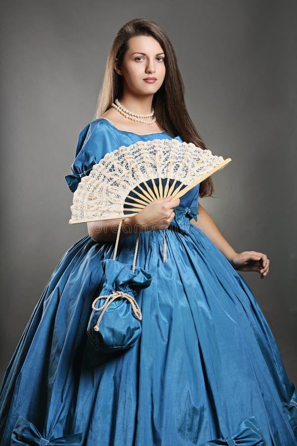 Bella donna con il costume ed il fan eleganti blu fotografia stock libera da diritti