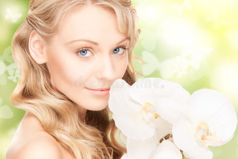 Bella donna con il fiore e le farfalle dell'orchidea fotografie stock libere da diritti