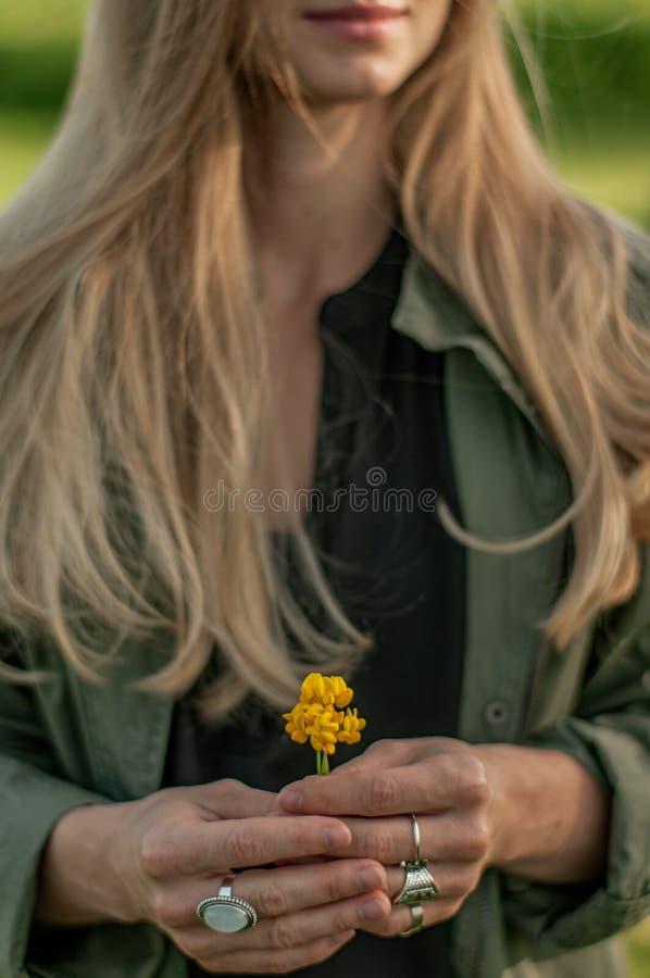 Bella donna con il fiore lungo della tenuta dei capelli Mani con gli accessori alla moda di boho degli anelli Nessun fuoco fotografia stock