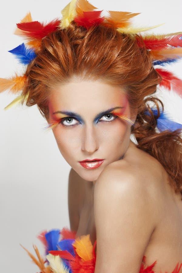 Bella donna con il fronte incorniciato in piume fotografia stock