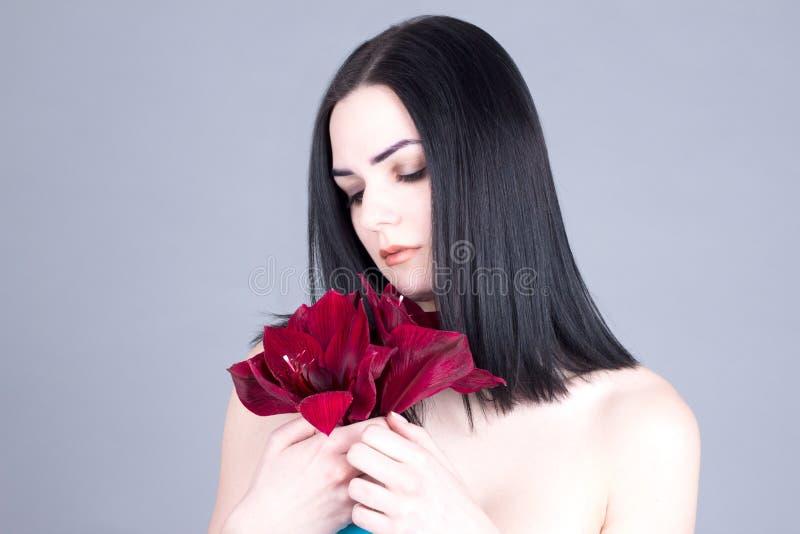 Bella donna con il fronte pulito, i capelli scuri ed il fiore rosso in mani immagine stock