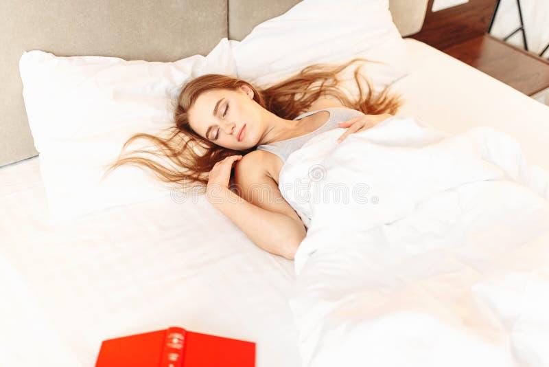 Bella donna con il libro che dorme nel letto fotografie stock libere da diritti