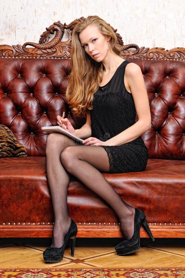 Bella donna con il libro che si siede sul sofà. fotografie stock