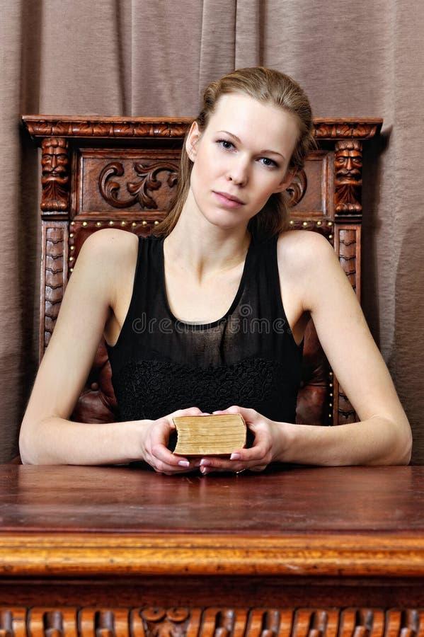 Bella donna con il libro nel salone. fotografia stock libera da diritti